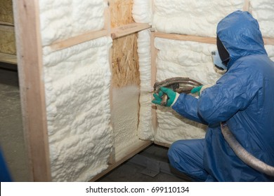The builder in a blue suit applies a construction foam from the gun to the wall of a wooden house