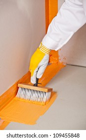 builder brush applied waterproofing on the floor of the bathroom