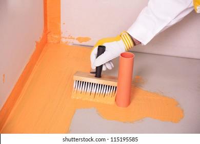 builder with brush applies waterproofing on the floor of the bathroom