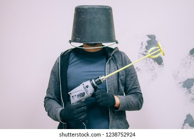 Builder with a bucket on his head holding a hand-held construction mixer