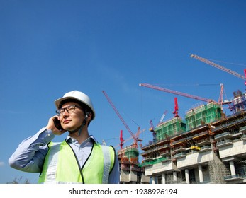 A builder calling on his cell phone in front of a building under construction in Singapore.