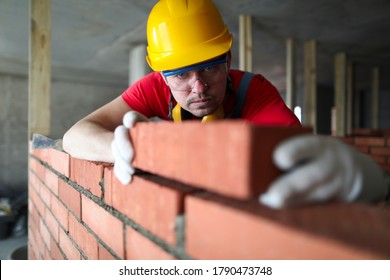 Builder carefully puts red brick on the masonry. Quick work bricklayer. Guy measures level masonry. Man is building brick wall. Correctly calculate material. Builder manually carries brick structure