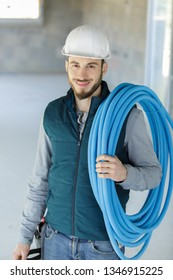 builder carrying reel of blue pipe on his shoulder