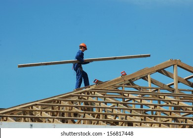 builder carrying timber for the roof framing