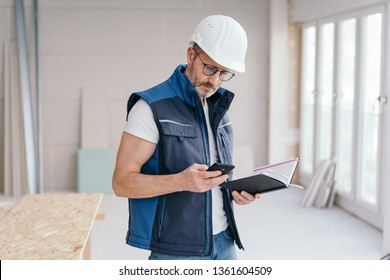 Builder checking a message on his mobile phone or making a call as he stands holding a journal on site in a new build house