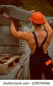 Builder concept. Builder unload truck. Builder in working uniform. Builder carry bricks. Safety comes first.