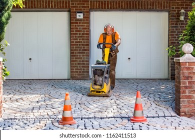 Builder or contractor laying new paving bricks in a house driveway using a mechanical compacter for compaction of the cement pavers.