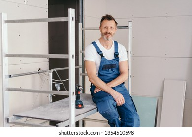 Builder in denim overalls relaxing on low scaffolding indoors in a new build house smiling at the camera in a renovation or DIY concept