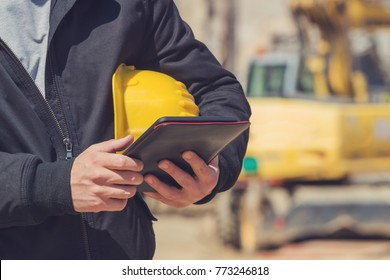 Builder with digital tablet posing on a heavy construction site.