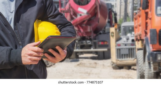 Builder with digital tablet working on a heavy construction site.
