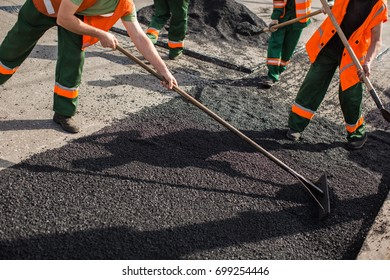 Builder during Asphalting road works level raw material before the operation of the machine