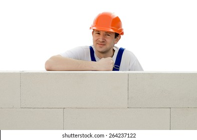 Builder erects a wall from a brick
