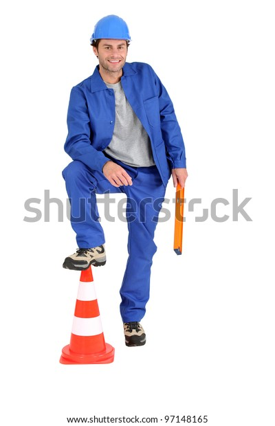 Builder with foot on cone.