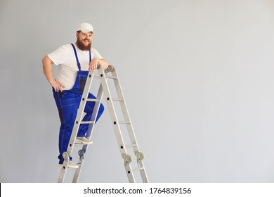 Builder funny man worker.Delighted male constructor on metal ladder.