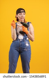 Builder girl in denim overalls and a black cap holds a drill and a screwdriver in her hands and poses on a yellow background