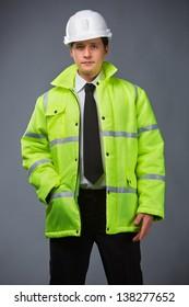 builder in a green jacket, helmet in hand pocket