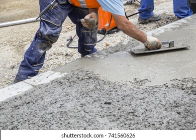 Builder hand leveling concrete with trowel, spreading poured.