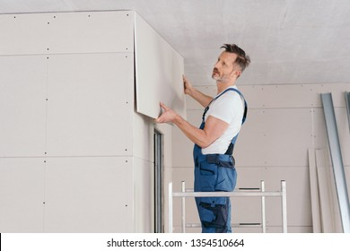 Builder or handyman fitting wall cladding inside a new build house standing on low metal scaffolding