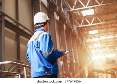 builder in hard hat looking at an industrial interior. Metal smelting plant