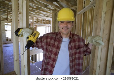 Builder in hardhat in partially built house, smiling, portrait
