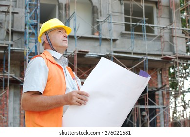 Builder in helmet with a drawing plan photo