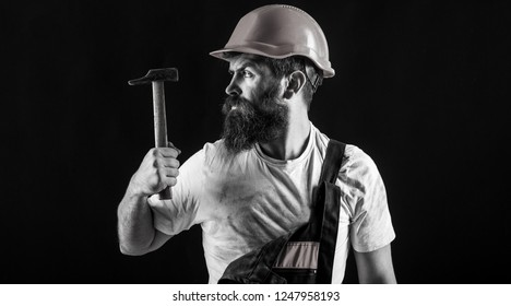 Builder in helmet, hammer, handyman, builders in hardhat. Handyman services. Hammer hammering. industry, technology, builder man, concept. Bearded man worker with beard, building helmet, hard hat.