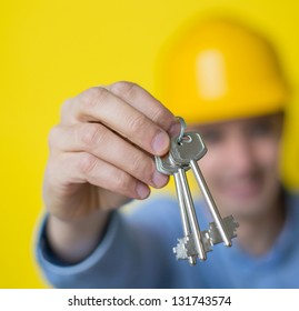 Builder in helmet hands keys to a new apartment