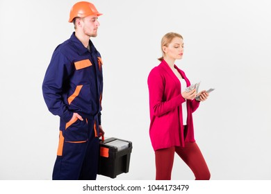 Builder in helmet looks at woman with busy face counting money, isolated on white background. Customer deceives repairman, builder, mechanic. Repairer, builder wants salary for work. Deceive concept.