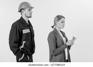 Builder in helmet looks at woman with busy face counting money, isolated on white background. Repairer, builder wants salary for work. Deceive concept. Customer deceives repairman, builder, mechanic.