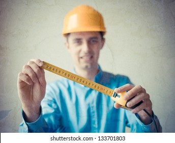 The builder in a helmet with a meter