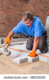 Builder installing new paving stones around a house leveling them with the aid of a spirit level and heavy hammer