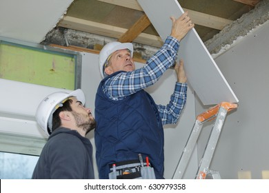 builder installing the rest of the drywall on the ceiling
