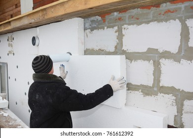 Builder installing rigid styrofoam insulation board for energy saving. Rigid extruded polystyrene insulation.