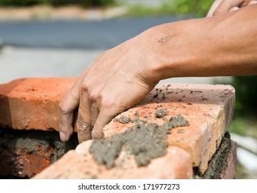builder laying bricks in site.