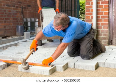Builder levelling paving stones as he lays them using a spirit level and heavy mallet or hammer as his assistant brings a new load behind him