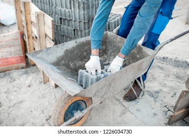 Builder loading paving tiles into the pushcart standing on the construction site, close-up view with no face