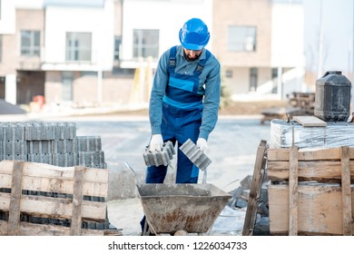 Builder loading paving tiles into the pushcart standing on the construction site
