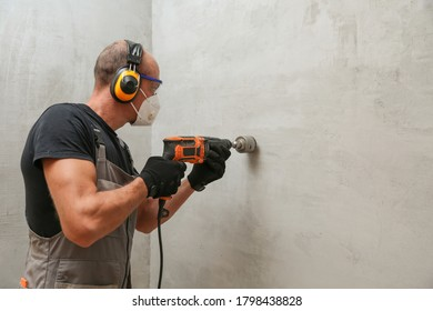 a builder makes a hole in the wall for an electrical outlet. contractor drilling wall with hammer drill