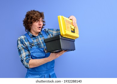 builder man opening tools box with shocked expression on face, curly caucasian guy in blue coveralls isolated over purple studio background. repairing concept