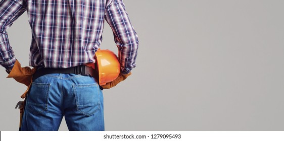 Builder man in plaid shirt and gloves wearing and holding helmet