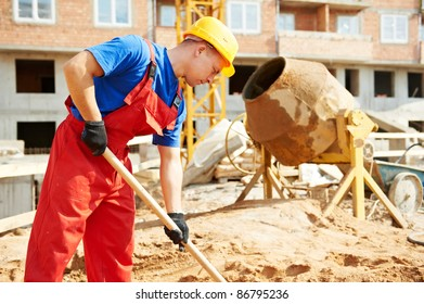builder man working with shovel during concrete cement solution mortar preparation at construction site