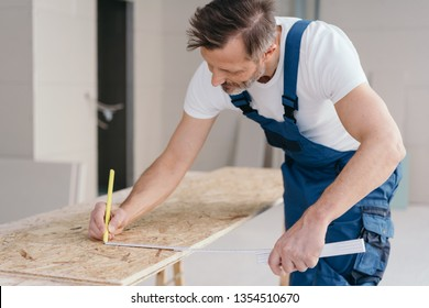 Builder measuring OSB sheet and marking it with pencil during building new house or renovation. Man in blue and white uniform working indoors