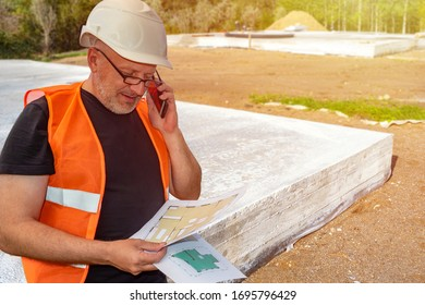 Builder next to foundation of the building. Builder is studying the drawings of the future home. Concept - architect calls customers. Architect near house foundation. Concept - construction company