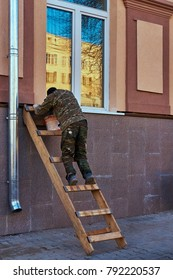 The builder on the stairs in the old stained clothes works