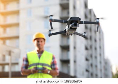 Builder operating drone with remote control at construction site, focus on quadcopter. Aerial survey