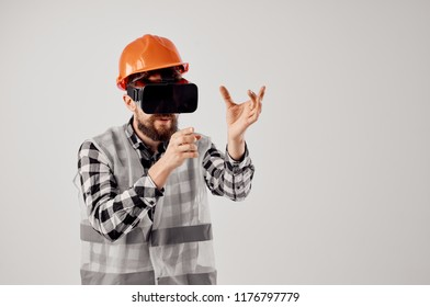 the builder in an orange helmet and in 3D glasses creates a three-dimensional shape building