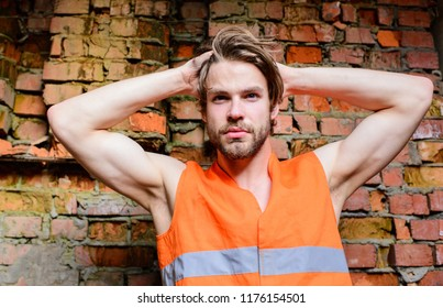 Builder orange vest work construction site. Sexy macho foreman. Builder sexy muscular arms macho dream of every woman. Guy tousled hair stand in front of wall made out of red bricks.