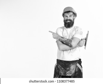 Builder, plasterer, repairman, foreman in helmet holds hands crossed, white background. Man with smile holds putty knife or tool, points with index finger, copy space. Repair advertisement concept.