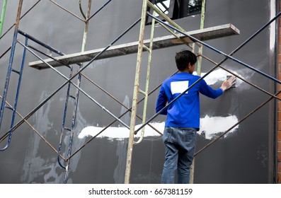 Builder plastering grey concrete wall with white plaster on building site