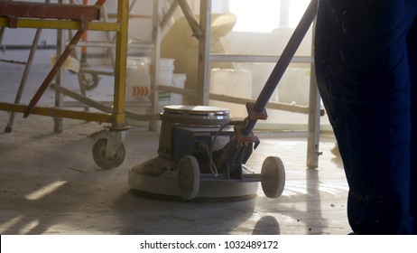 Builder polishing mortar floor at construction site of new appartments. Mechanized grout screed concrete floor close-up. Laborer performing and polishing sand and cement screed floor.